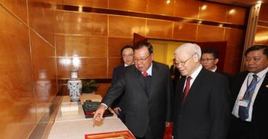 Tổng Bí thư Nguyễn Phú Trọng và Tổng Bí thư, Chủ tịch nước Lào tham quan triển lãm ảnh về tình đoàn kết Việt - Lào