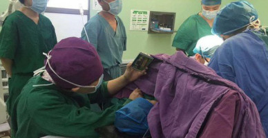 Y tá ân cần quỳ bên bàn mổ suốt cả tiếng đồng hồ để cầm điện thoại cho bệnh nhi xem hoạt hình