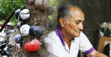 Chuyện về cụ ông Hà Nội phía sau cây cổ thụ treo hàng chục chiếc mũ bảo hiểm sứt mẻ trên đường Trần Hưng Đạo
